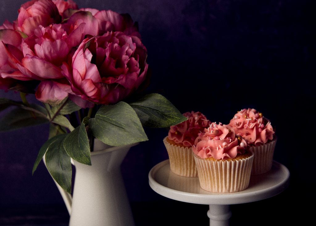 perfect product photos, cupcakes with pink frosting placed on a table alongside a vase full of pink roses