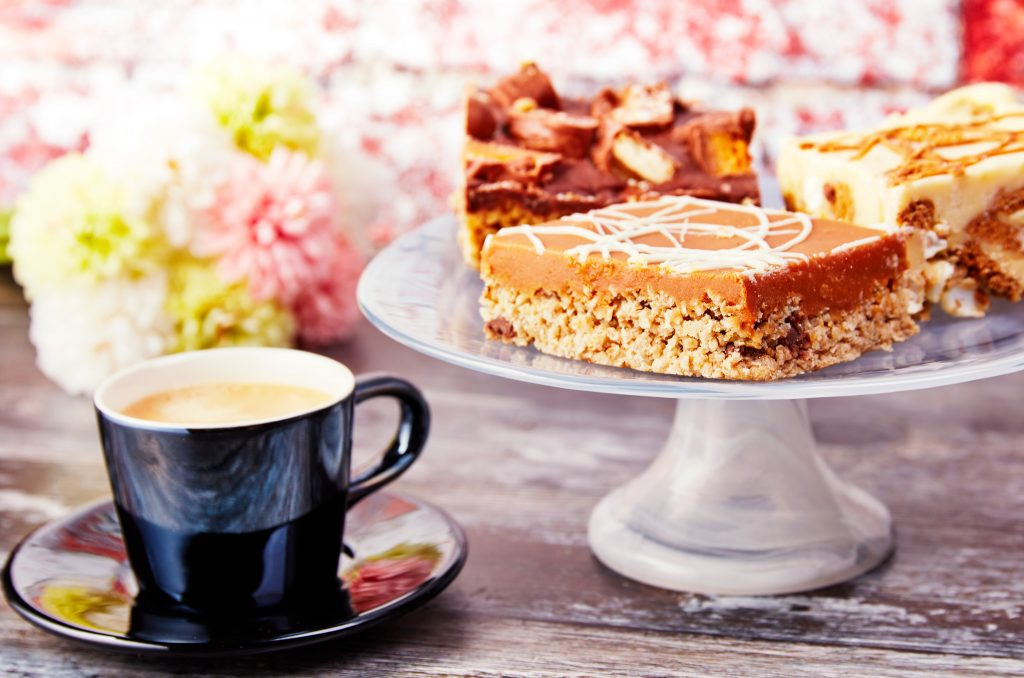 coffee and dessert placed on a table alongside different flowers in the background