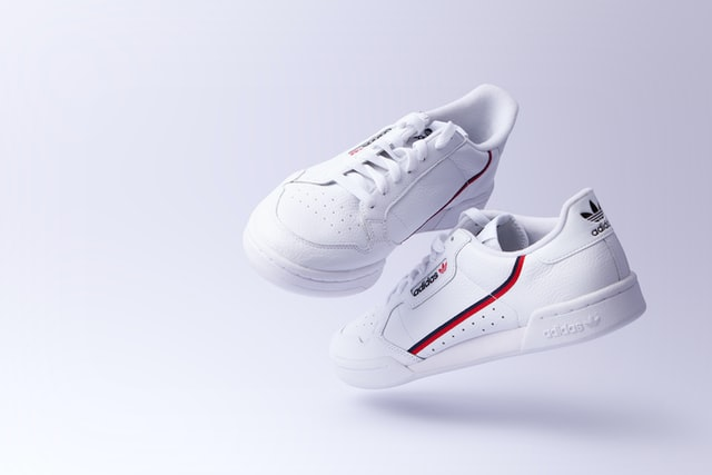 capture perfect product photos, product photography shoot of branded white sneakers with a white background