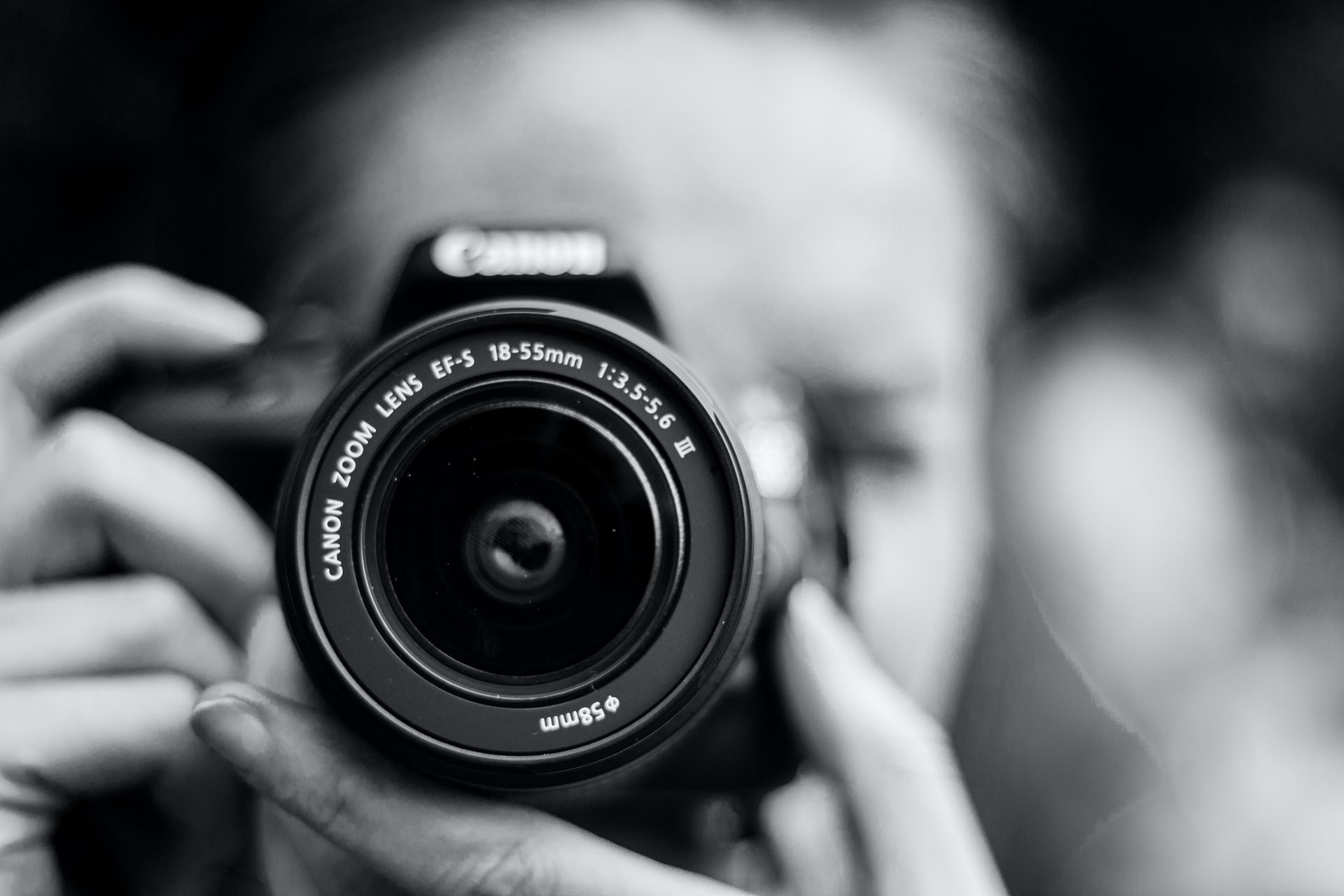 professional website imagery; a closeup of a photographer's camera lens shot in monochrome