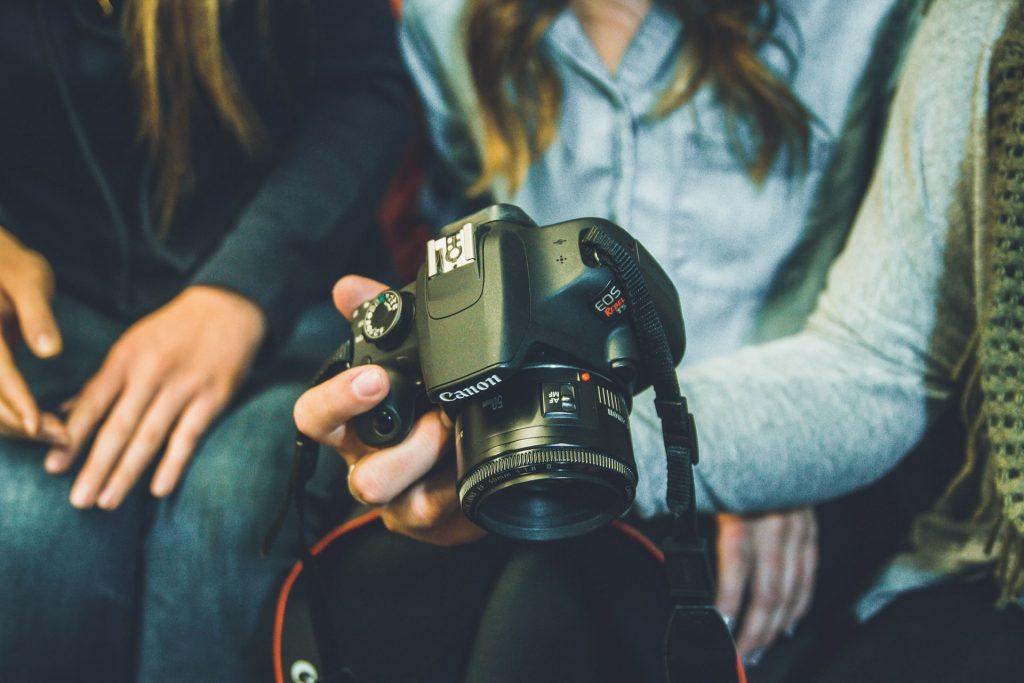With Event Photography services and a few photography tips in mind, your event is sure to be a massive success; a group of people sitting together with one of them holding a professional camera