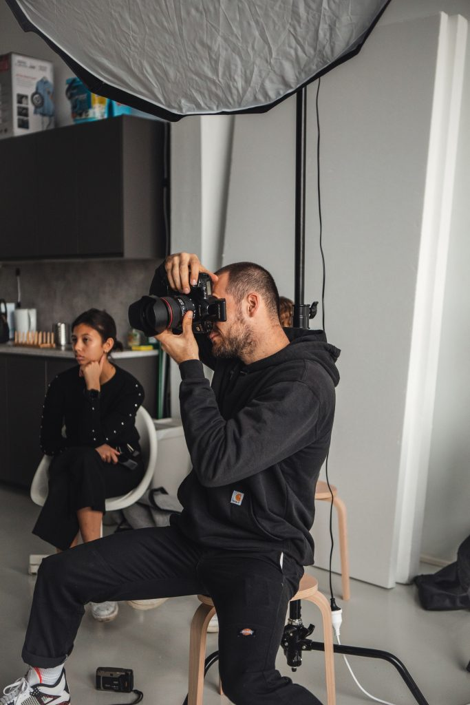 Scheduling a test run can help you understand the photographer's process while also giving you an example of what the images will look like; a photographer sitting on a stool focusing his camera on a subject