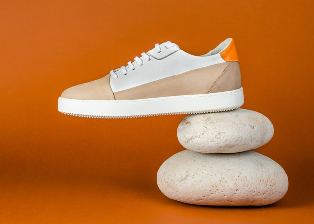 Small business commercial photography; brown shoe placed on a couple of pebbles with an orangish brown background