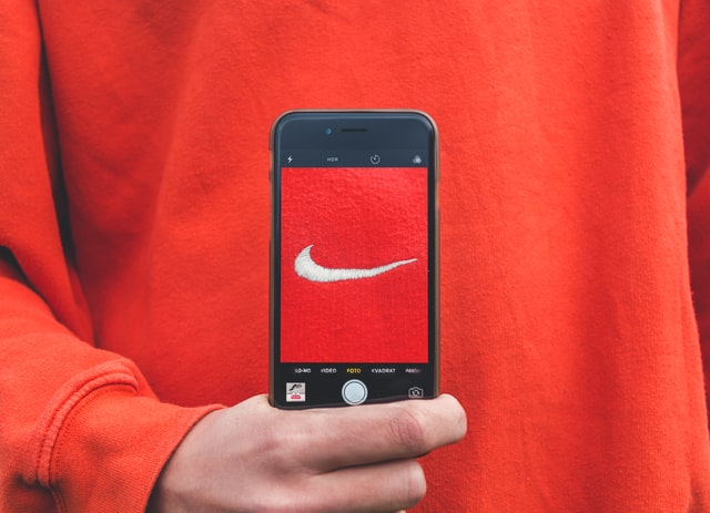 Small business commercial photography; person holding an iPhone with nike logo on its display