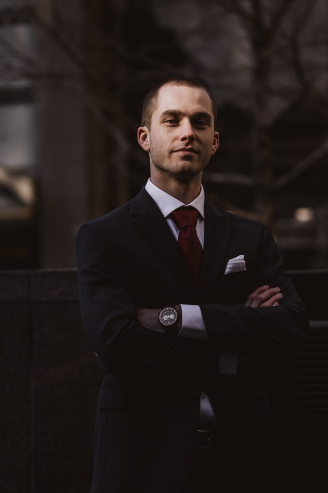 Social media headshots; man wearing a black suit and maroon tie standing with his hands crossed