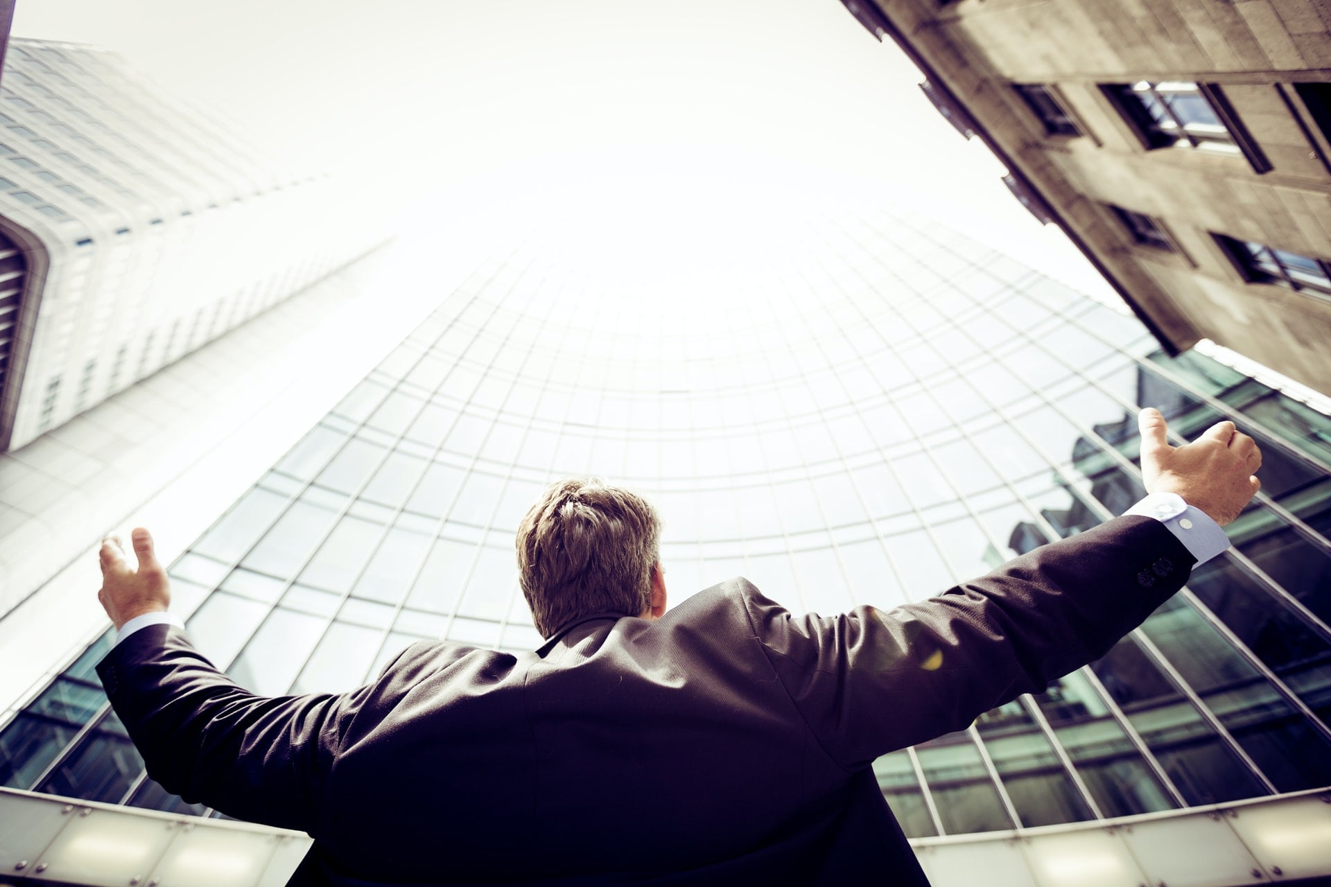 small business commercial photography; man standing with his arms wide open while looking at the building in front of him