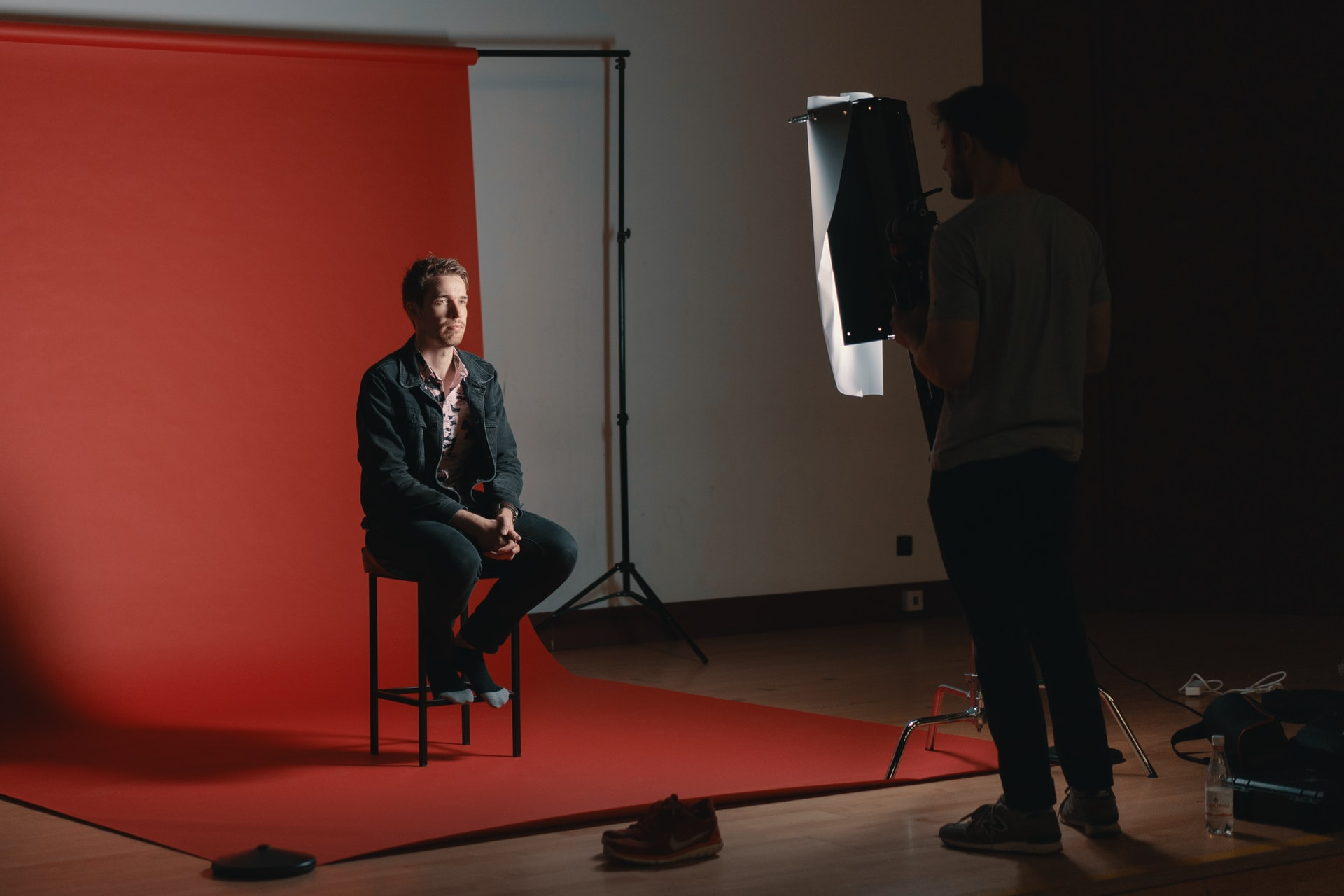 leverage business headshots; a person getting their headshot taken in a studio, against a red background