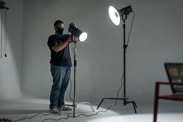 photographer adjusting lights in a photo studio