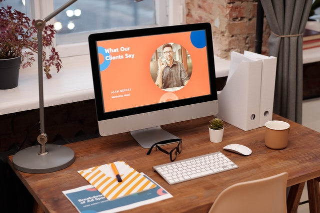 leverage business headshots; a website with a clear headshot photo opened on a computer placed on a wooden table