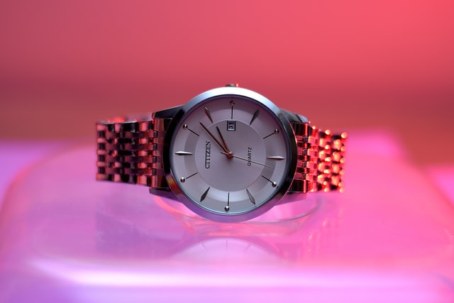 an aesthetic picture of a watch placed horizontally with neon pink and purple lights in the background