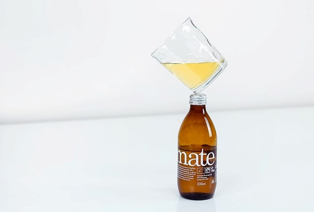a product shot of a bottle with a glass balancing on top